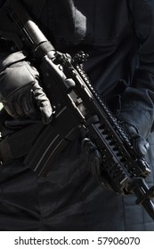 Automatic big black gun in hands of soldier in black uniform. Close up, weapon details. Unknown soldier