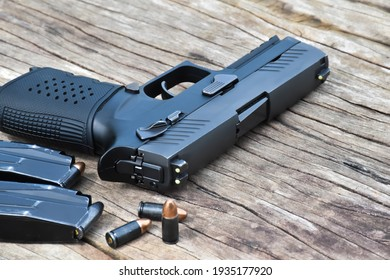 Automatic black 9mm pistol, ammunitions and cartridges on wooden table. Selective focus specific on gun.