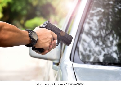 Automatic black 9mm pistol holding in hands aimed at the pickup windshield, concept for robbery, safety, security, bodyguard, mafias, gangster and the hijack.