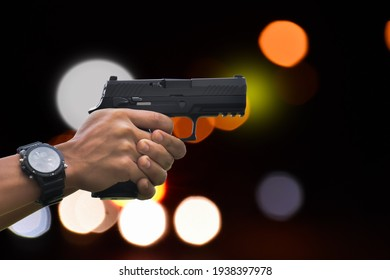 Automatic black 9mm pistol holding in hand aiming to specific destination and ready to shoot with street light bokeh background, concept for robbery, security, bodygourd, mafia and gangster at night