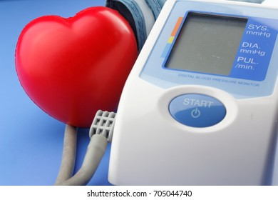 Automatic blood pressure monitor on a table with heart shape symbol. Concept of health,insurance and catdiovascular health.