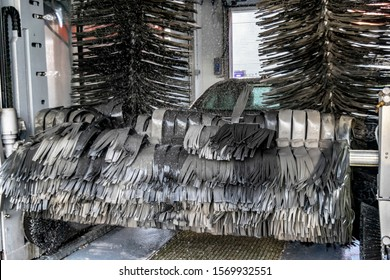 Automatic brushes wash the car. Industrial carwash with soapy foam.