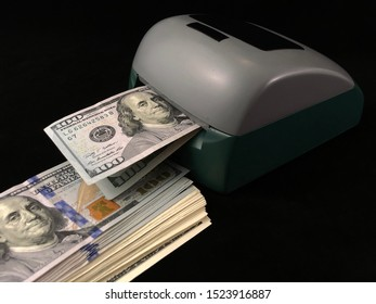 Automatic detector for checking banknotes. Dollars are checked through the device. One hundred dollar bills and a machine for counting money. Concept: fake money, fake american dollars