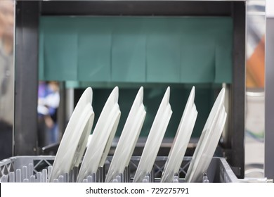 The automatic dishwasher with white clean dishes in basket .For restaurant. food industrial background