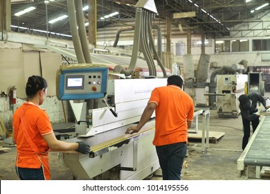 The automatic Edge Banding Machine with worker at the furniture factory.