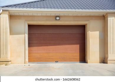 Automatische elektrische Roll-Up-Gate oder Haustür im modernen Gebäude Erdgeschoss . Tür- oder Rollentür und Betonboden außen. Braune automatische Fensterläden in einem Haus. Tore in der Garage