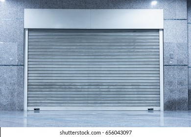Automatic Factory Shutter Roller Door Indoor, Steel Rolling Gate Door for Security System of Warehouse Storage. Architecture Metal Access Doorway With Granite Wall Background of Workshop Garage.