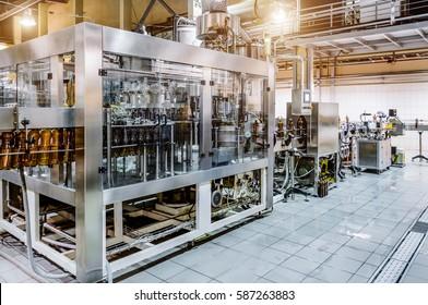 Automatische Füllmaschine. Bier in einer Brauerei gießen. Spot-Lichteffekt