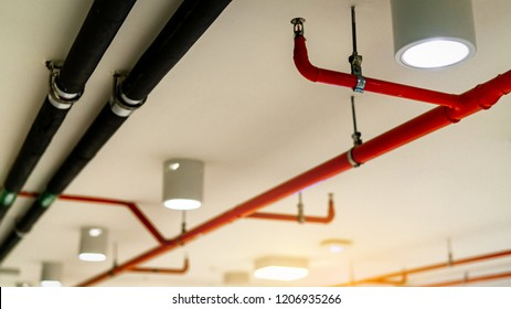 Automatic fire sprinkler safety system and black water cooling supply pipe. Fire Suppression. Fire protection and detector. Fire sprinkler system with red pipes hanging from ceiling inside building.