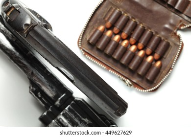 The automatic gun and plastic toy gun put beside with full load of old and dirty spare pistol bullet as background represent the weapon and bullet concept related idea.