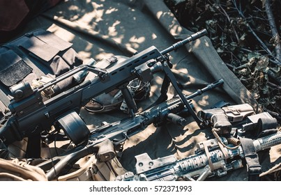 Automatic, hand gun, machine gun, helmet and body armor piled in a heap, lying on the ground. The zone of military operations.