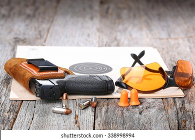 Automatic Handgun with leather holster, bullets and safety glasses on a wooden background.