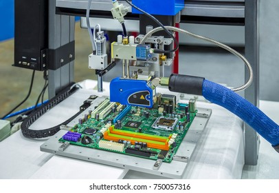 Automatic Hot Melt Glue Applicator and Adhesive Dispensing Gun with Auger Valve Dispensing Solder onto a PCB in the Electronics Industry.