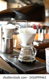 Automatic hot water machine dripping into a ceramic pour over cone and glass coffee carafe, in a gourmet beverage concept