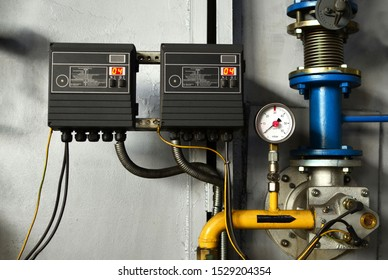 Automatic industrial burner control unit. Round mechanical pressure gauge for measuring pressure. Gauges in the boiler room near the heating pipes with insulation coating. Oil and gas pipeline