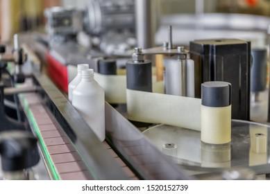 Automatische Linie für das Füllen und Etikettieren von Arzneimitteln. Der Mechanismus zum Kleben von Etiketten.