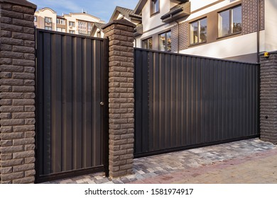 Automatic metal gates with decorative brick columns on the street side.
