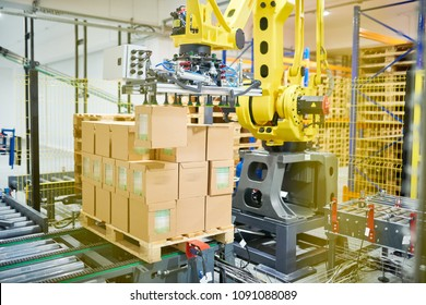 Automatic packaging machine working upon pile of cardboard boxes, interior of spacious warehouse on background