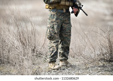 Automatic rifle detail and military camouflage uniform on a soldier in a field