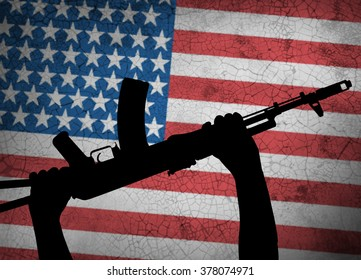 Automatic rifle in hand on background of the American flag