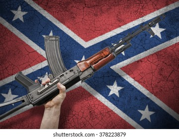 Automatic rifle in hand on background of the flag of the Confederate States of America