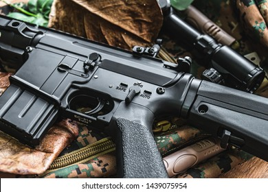 Automatic rifle Place on the ground with dry leaves as a background. A BB gun Also known as airsoft gun, used with round plastic pellets