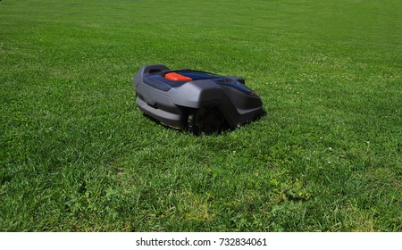 Automatic robot lawnmower mows grass on green lawn