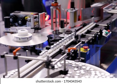 Automatic self-adhesive labeling machine for medicine bottles for injection. Selective focus.