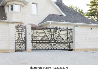 Automatic sliding gates of white color with ornament from black wrought metal