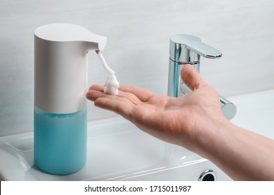 Automatic soap dispenser in the bathroom. Hand with soapy solution closeup