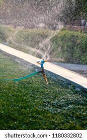 Automatic spinning sprinkler working in park spraying water in air