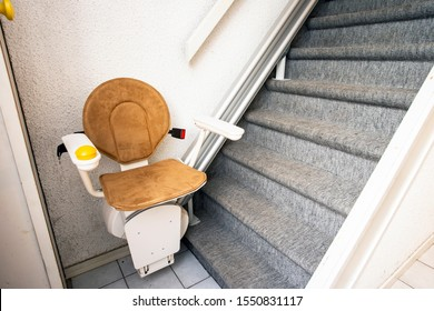 Automatic stair lift on staircase taking elderly people and disabled persons up and down in a house close-up