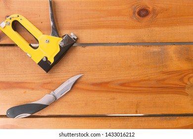 An automatic staple gun and a pocket knife are laying on a wooden surface