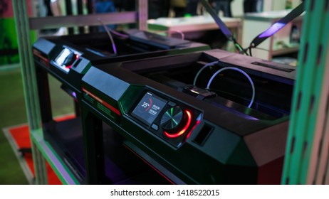 Automatic three dimensional 3D printer machine working at modern technology exhibition. 3D printing, additive technologies, 4.0 industrial revolution and futuristic concept