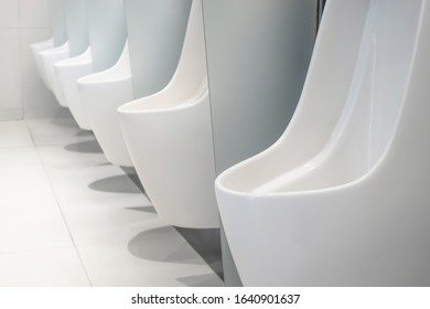 Automatic urinals in the men's bathroom. Automatic cleaning system in male toilet.