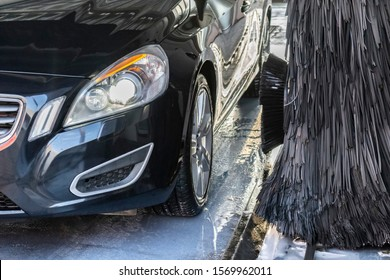Automatic washing of a black luxury car. Part of a car in white soapy foam.