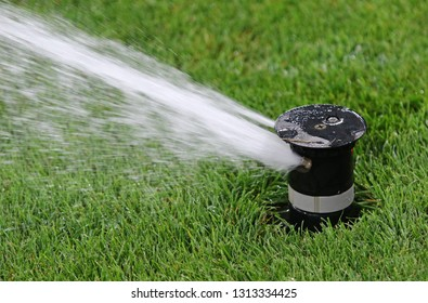 Automatic water irrigator in action. Close-up sprinkler of automatic watering. Green grass soccer field