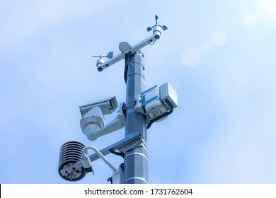 Automatic weather station, with a weather monitoring system and video cameras for observation. Against the background of blue sky clouds. - Shutterstock ID 1731762604