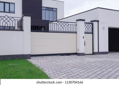 Automatic white gate with forged elements in the family house