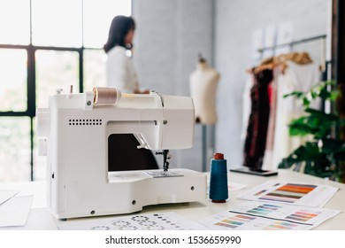 Automatic white sewing machine and patterns on table in workshop studio with blurred female stylist on background