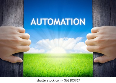Automation. Hand opening an old wooden door and found Automation word floating over green field and bright blue Sky Sunrise.