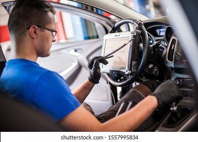 Automobile Computerdiagnose. Automechaniker suchen nach einem Triebwerkausfall in der Diagnoseeinrichtung in der Werkstatt für die Fahrzeugwartung
