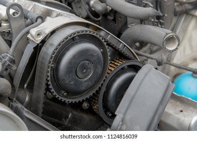 Automobile engine with side cover removed, exposing an old, cracked timing belt