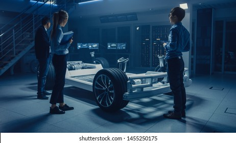 Automobile Engineers Working on Electric Car Platform Chassis, Using Tablet Computers with CAD Software for 3D Concept. In Automotive Innovation Facility Vehicle Frame with Wheels, Engine and Battery