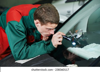 Automobile glazier repairman repairing windscreen or windshield of a car in auto service station garage
