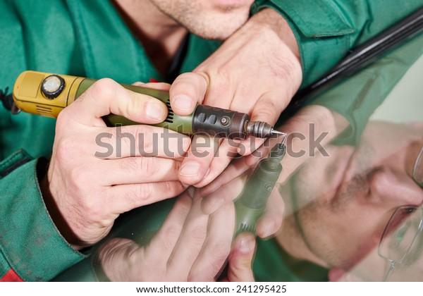 Automobile glazier repairman at windscreen repair of a car in auto service station garage