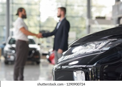 Automobile headlight and men standing behind. Car dealer and client of car dealership shaking hands. Manager and customer making deal on purchasing vehicle. Modern auto showroom.