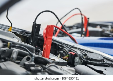 Automobile help. booster jumper cables charging automobile discharged battery