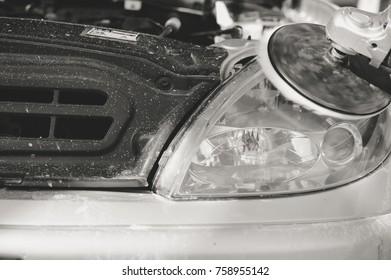 Automobile industry. Close up on car detail - male hand polish in auto repair shop background. Professional person during mechanical maintenance, industrial part transport renovation