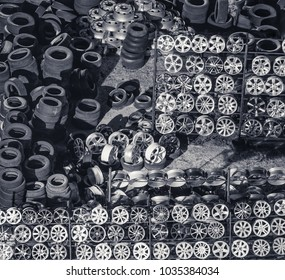 Automobile new and old tires and rims, folded rows of warehouse, in storage outdoors, Russia. View from above.